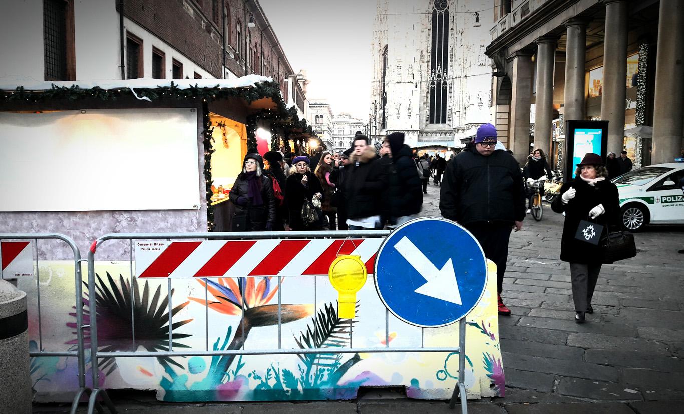Difficile scorgere un murale dietro la segnaletica in Piazza Fontana
