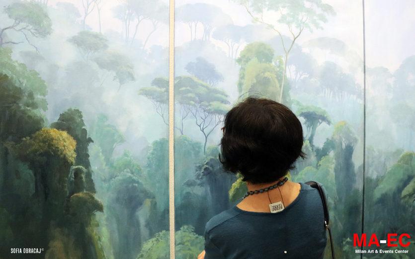 Una visitatrice osserva un paesaggio dipinto di Jorge Cavelier